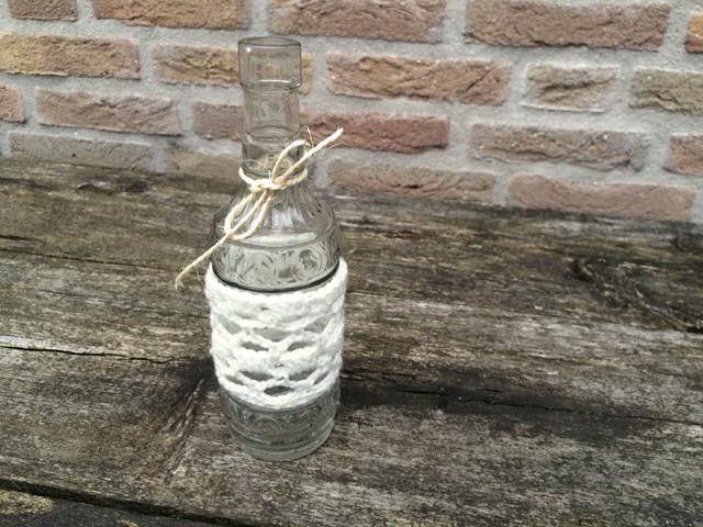 Haken om een fles met wit wol